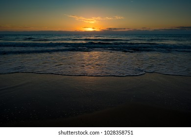 sunset or sunrise on the sea with a sandy beach. Calm sea at dusk