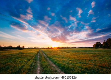 Sunset, Sunrise Over Rural Meadow Field. Bright Dramatic Sky And Country Road Path Way. Countryside Landscape Under Scenic Summer Dramatic Sky In Sunset Dawn Sunrise. Skyline.