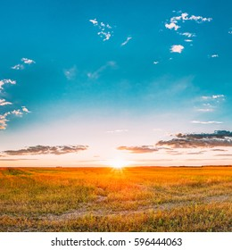 Sunset, Sunrise Over Rural Meadow Field. Bright Dramatic Sky Over Countryside Landscape Under Scenic Summer Dramatic Sky In Sunset Dawn Sunrise. Sun dawn Over Skyline Or Horizon.