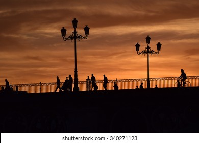 A sunset is surrounding a beautiful bridge in Seville during a warm and late summer evening.