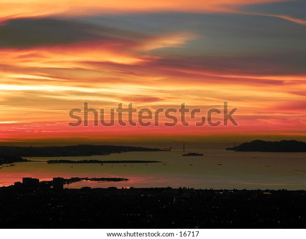 Sunset taken from the Oakland hills over Berkeley and Emeryville towards San Francisco and the Golden Gate Bridge. Treasure and Alcatraz Islands are visible in the Bay; a tiny outline of the Farallon Islands is barely visible over the South Bridge tower.