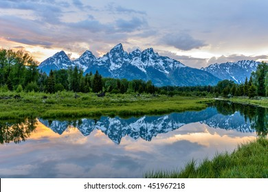 Sunset Teton Range at Snake River - Spring sunset view of Teton Range reflecting in calm Snake River in Grand Teton National Park, Wyoming, USA.