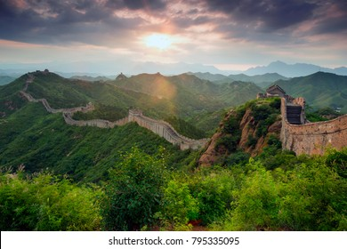 Sunset through dark ominous storm clouds over the Great Wall of China at the wild wall in Jinshanling