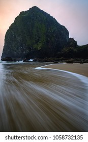 Sunset through the fog at Cannon Beach in Oregon with a fast moving wave in the foreground.