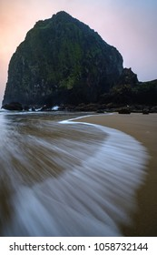 Sunset through the fog at Cannon Beach in Oregon with a snaking wave weaving a leading line through the foreground of the image.