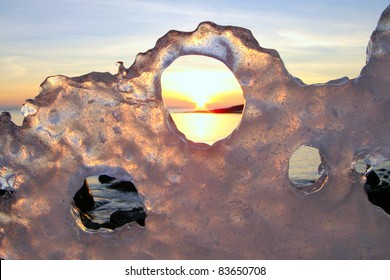 Sunset through ice's holes in Finland