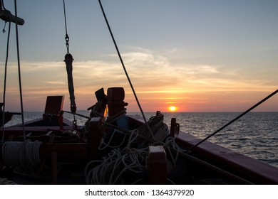 Sunset through the rigging of an old, wooden sailboat in the Andaman Sea of Thailand