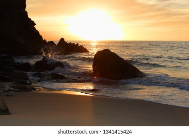 Sunset through rocks on a sandy beach