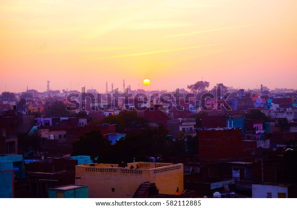 Sunset time in Agra, India. View from the roof. Awesome sunset, bright and warm colors. Urban landscape.