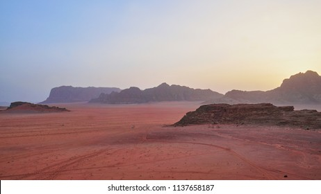 Sunset time rocks in Wadi Rum desert (The Valley of the Moon). Jordan, Middle East.  Red sands, sky with haze. Designation as a UNESCO World Heritage Site.