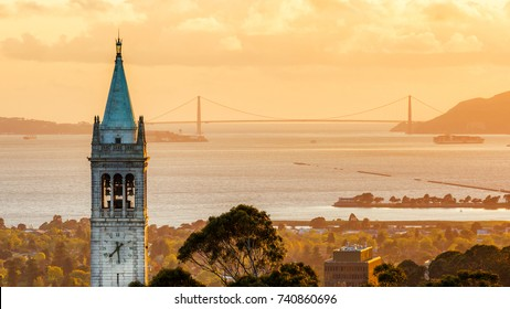Sunset time Sather Tower at University of California, Berkeley campus, with Golden Gate Bridge in the background.