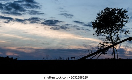 Sunset with tree and equipment silhouette