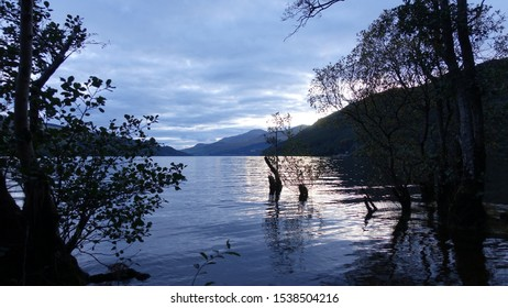 Sunset with trees and reflections over Loch in Scotland