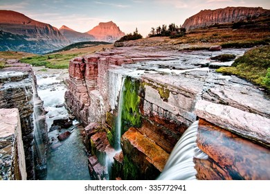 Sunset at Triple Falls in Glacier National Park: Montana, USA.