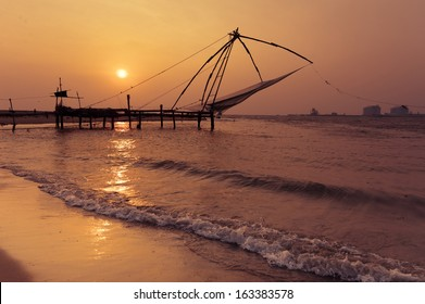 Sunset at tropical beach. Ocean coast landscape with chinese fishing nets silhouette at Cochin (Kochi). South India, Kerala, Kochin