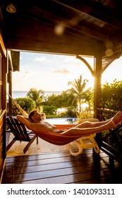 Sunset tropical beach St Lucia Caribbean, men hammock watching sunset