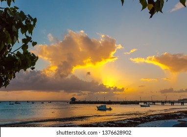 Sunset at the tropical coast with boats and clouds