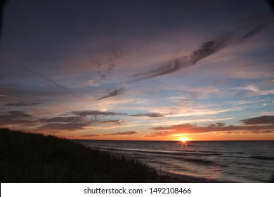 Sunset from a tropical desert beach with pastel colors, clouds and reflection in sand
