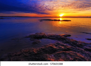 Sunset of Truman Lake, located as part of the Lake of the Ozarks in Missouri.  Has colorful sky and rocky shoreline