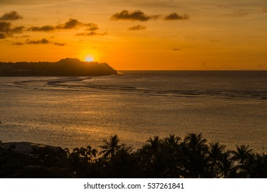 Sunset at Tumon Bay in Guam, USA. The sun is just setting at Ypao Point and the sky is getting dyed red. Tumon Bay is one of the most famous tourist attractions in Guam.