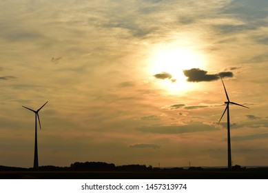 Sunset with two wind turbines and wide landscape