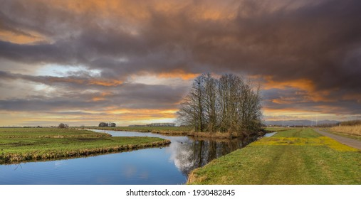 Sunset typical Dutch polder landscape in polder Zaans Rietveld along N11 in the municipality of Alphen aan den Rijn with green meadows surrounded by ditches and plots with trees