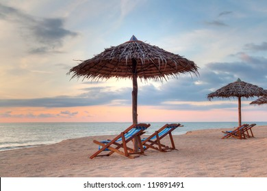 Sunset under parasols on the beach, Thailand