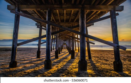 Sunset Under The Pier, Newport Beach, CA - Shot just before sunset which rendered long shadows from the support posts under the pier