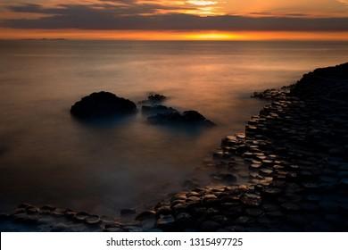 Sunset and unique shaped coastal rocks at Giants Causeway, North Ireland
