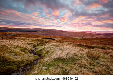 Sunset view across moorland to the Pennines in the Yorkshire Dales. The distinctive, plateaued peak of Ingleborough, one of the famous three peaks, can be seen on the horizon.