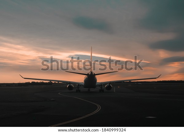 Sunset view of an airoplane on airport runway under the dramatic sky in Prague Czech republic. Aviation technology and world travel concept
