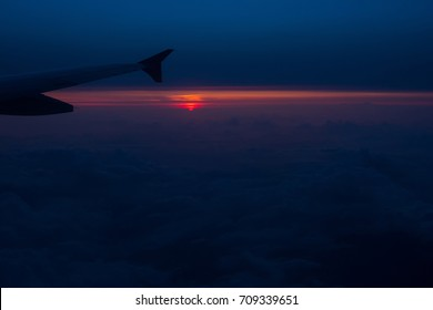 Sunset view from an airplane. Flying over the clouds in colorful sunset