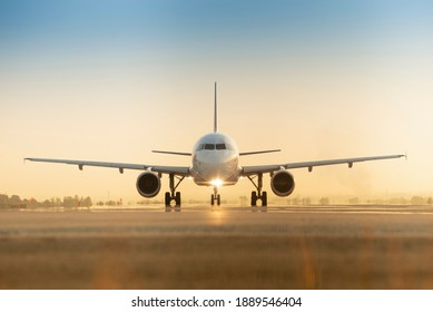 Sunset view of airplane on airport runway under dramatic sky