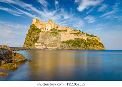 Sunset view of Aragonese Castle or Castello Aragonese - famous landmark and tourist destination near Ischia island, Italy. Long exposure daylight image