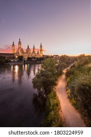 """Sunset view  of the """"Basilica del Pilar"""" in zaragoza. with a road and the moon."""