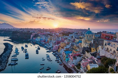 Sunset view of beautiful Procida. Colorful houses, cafes and restaurants, fishing boats and yachts in Marina Corricella, glowing sky and serene sea in Procida Island, Italy.