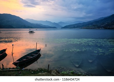 A sunset view of boats on the shore of and under the surface of Phewa Lake near Pokhara Nepal