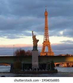 Sunset view of both The Eiffel Tower and The Statue of Liberty in Paris while having an open-air tour of the City of Light from along the River seine . France.