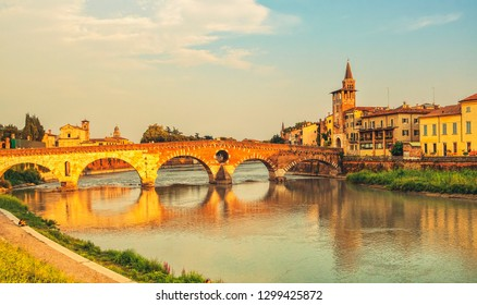 Sunset view of Bridge Ponte Pietra in Verona on Adige river, Veneto region, Italy.