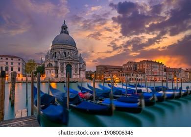 Sunset view of Canal Grande with Venice gondola and Basilica di Santa Maria della Salute in Venice, Italy. Architecture and landmarks of Venice. Venice postcard