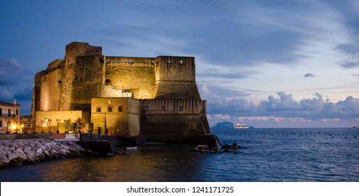 Sunset view of Castel dell'Ovo over the sea in Naples, Italy.