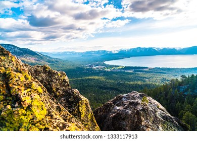 sunset view from castle rock peak above majestic landscape of Sierra Nevada mountains and Lake Tahoe Wilderness in enchanted thick forest of pine trees and sequoia trees in Northern California