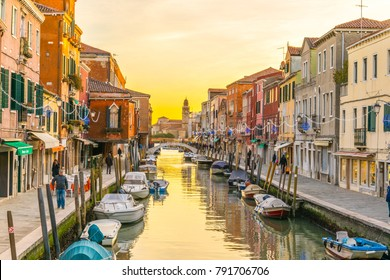 Sunset view of a channel on murano island in italy which is surrounded with tourist shops selling famous murano glass