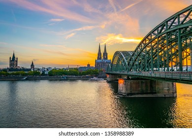 Sunset view of cityscape of Cologne with Hohenzollern bridge, cathedral and Saint Martin church, Germany