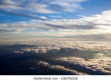 The sunset view with clouds beneath flying high over Atlantic Ocean.
