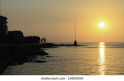 Sunset view of the Corniche Beirut, a seaside promenade in Beirut, Lebanon, silhouetted against the colourful golden sky
