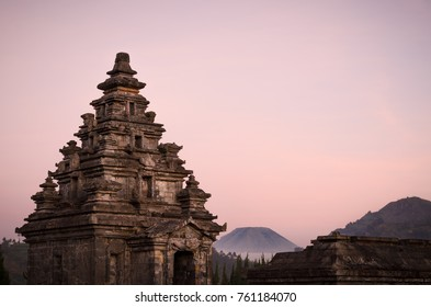 Sunset view of Dieng plateau with ancient stone hindu temple and volcano, in Java, Indonesia.