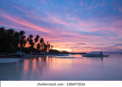 Sunset view of the Dolho Beach with traditional bangka boats, Panglao, Bohol, Philippines