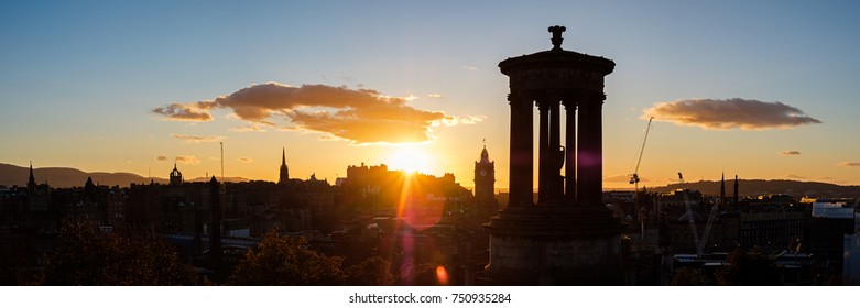Sunset view of Edinburgh's skyline with the iconic Dugald Stewart Monument in the foreground and the Edinburgh Castle at the back. Scotland, UK