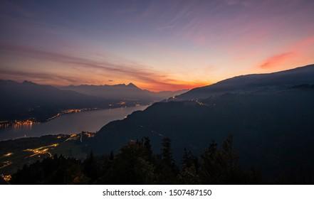 sunset view from Harder Kulm with lights around lake Thun